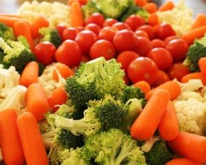 Alimentos ricos em vitamina K, como espinafre, cenoura e tomates.